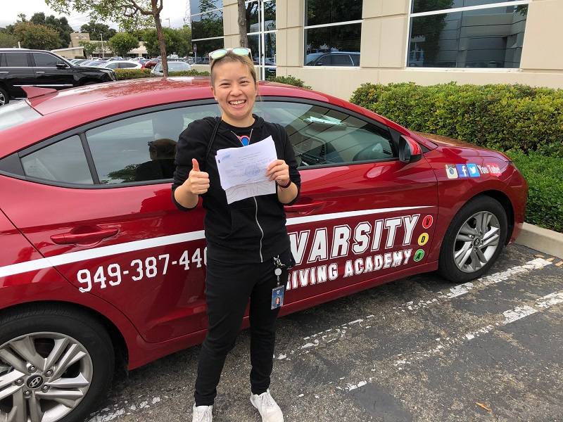 How to Choose a Driving School in Orange County Female Student Standing Next to a Training Vehicle