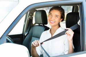 young woman in a car fastens seat belt