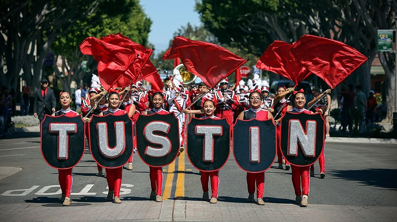 Where to Take your Drivers Ed Test in Tustin Teen Girls Walking in a Parade Holding Lettering Spelling Out Tustin