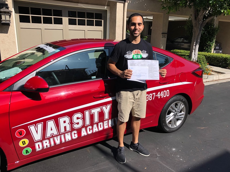 Best Driving Lessons in Lake Forest Student Standing Next to Training Vehicle