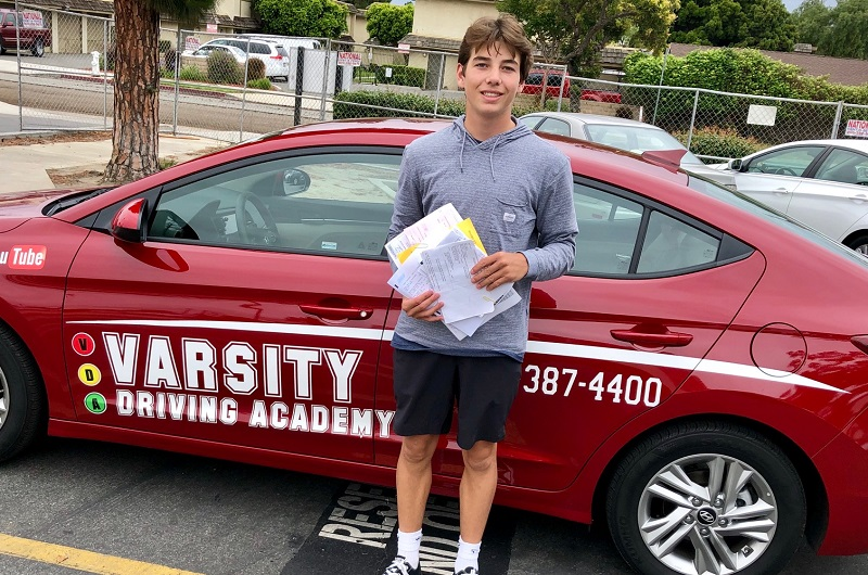 Irvine Driving Lessons Male Student Standing Outside of a Training Vehicle