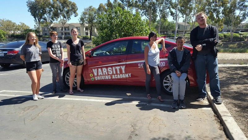 Where to Take Driving Lessons in Newport Beach Teens Standing Around a Training Vehicle
