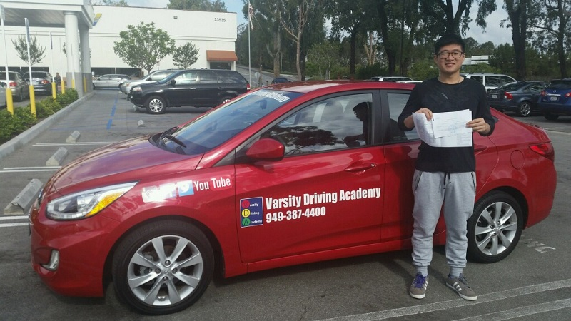Where to Take Driving Lessons in Huntington Beach Student Standing Next to a Training Vehicle