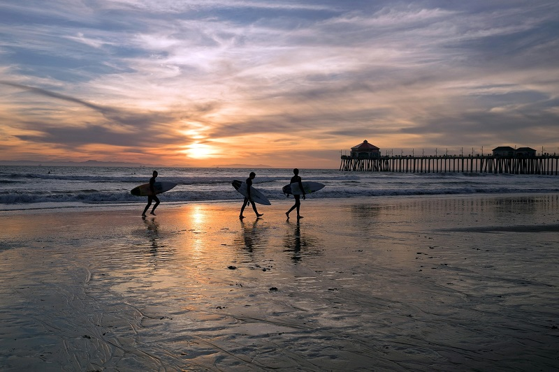 Where to Practice Driving in Huntington Beach Surfers Walking on a Beach