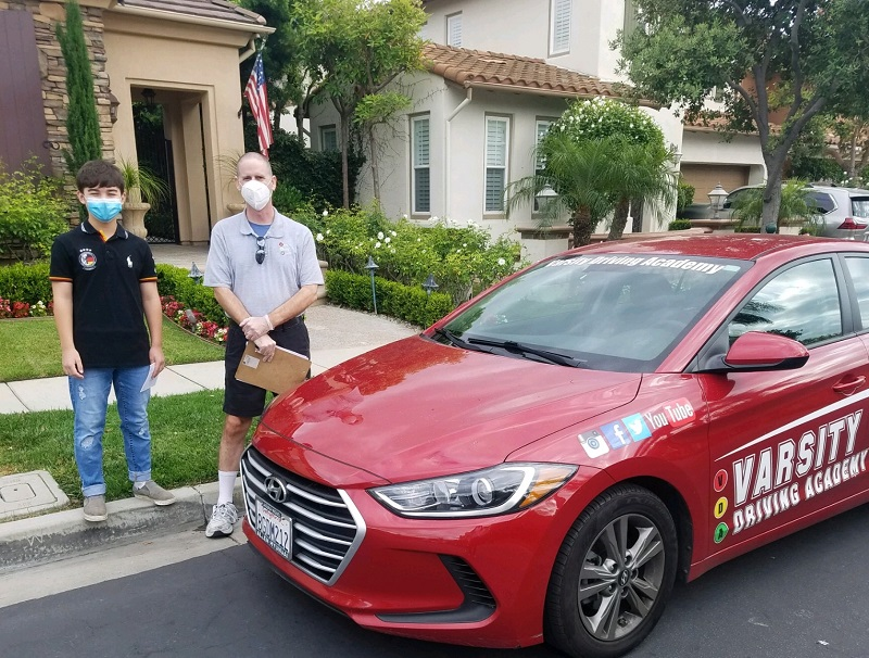Dana Point Driving Lessons Student and Trainer Standing Next to a Training Vehicle