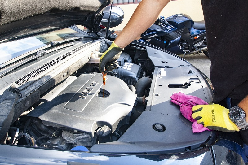 What is a Car Tune Up Person Working on the Engine of a Car