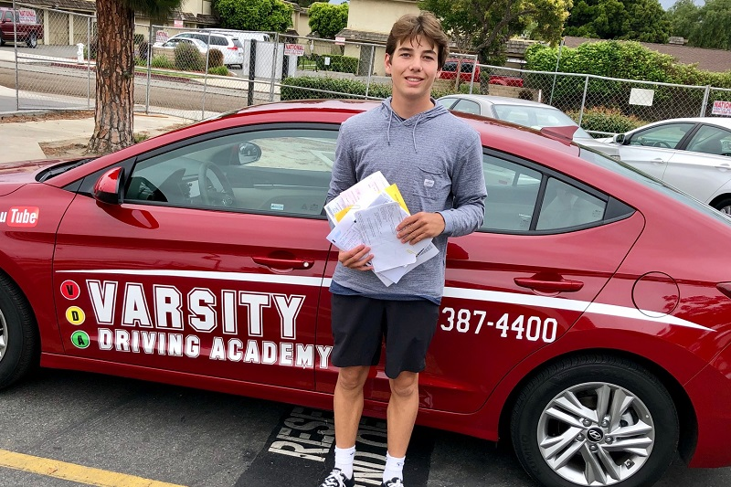 Laguna Niguel Driving Lessons Male Student Standing Next to a Training Vehicle in a Parking Lot