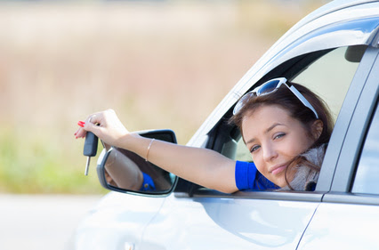 woman in a car holding keys in hand